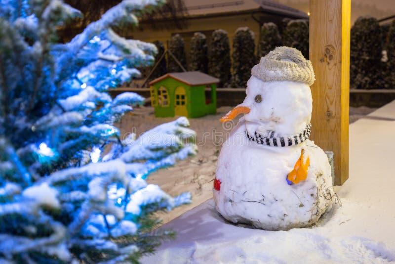 Kerstboom en sneeuwman openlucht bij sneeuwnacht stock fotografie