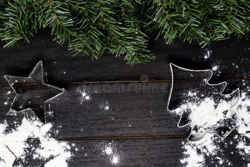Kerstboom en sterkoekjessnijder op houten achtergrond stock foto