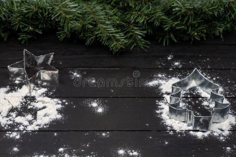 Kerstboom en sterkoekjessnijder op houten achtergrond met bloem royalty-vrije stock fotografie