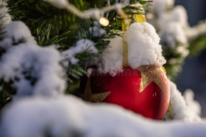Kerstboom met slingerlichten en rode ballen wordt verfraaid die royalty-vrije stock afbeelding