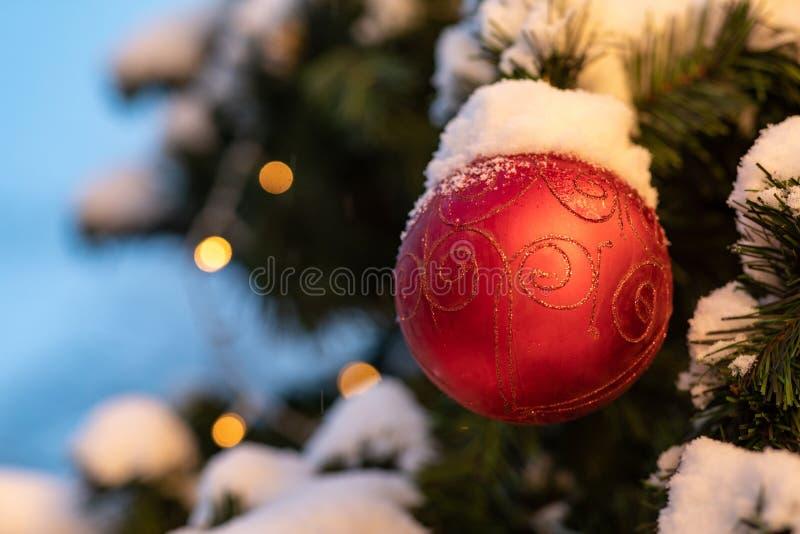 Kerstboom met slingerlichten en rode ballen wordt verfraaid die stock foto