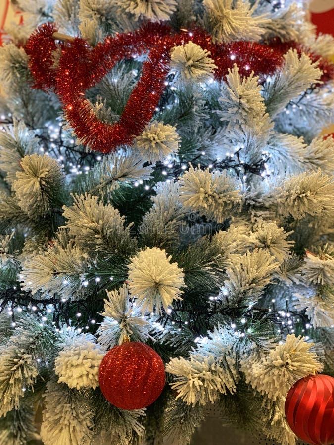 Kerstboom met sneeuw wordt met rode schitterende ballen en het gloeien lichten wordt verfraaid behandeld dat royalty-vrije stock foto's