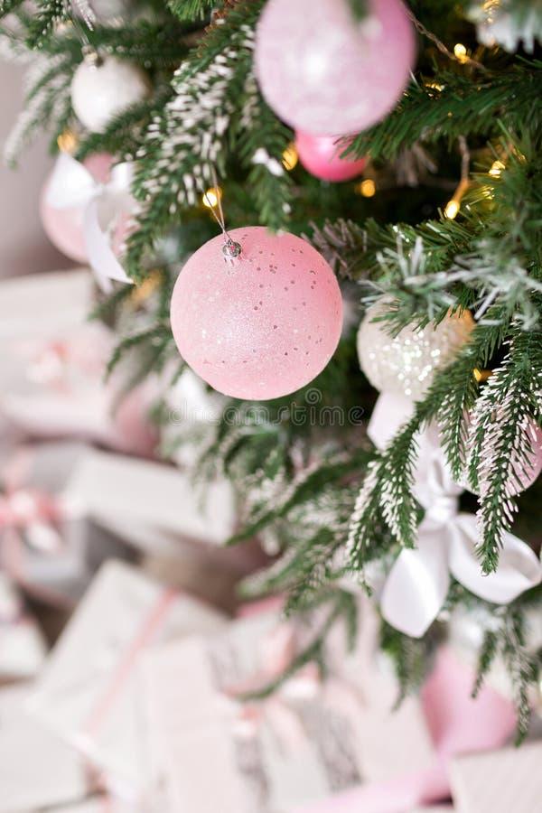 Kerstboom met speelgoed in zilveren en roze kleur wordt verfraaid die Daarin zien wij de ballons met van linten en lichten royalty-vrije stock afbeeldingen