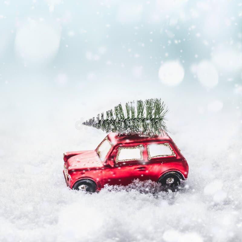 Kerstboom op rode stuk speelgoed retro auto in sneeuw, door sneeuw de winterwonder land met sneeuwval en bokeh royalty-vrije stock afbeeldingen