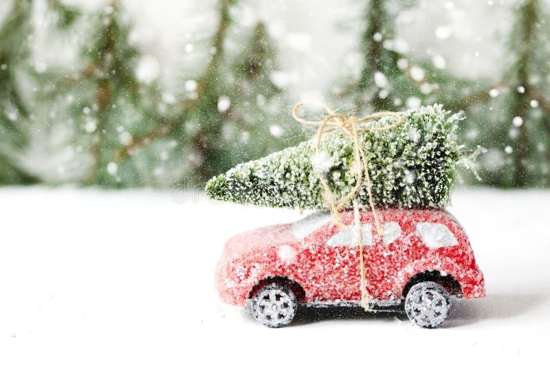 Kerstboom op rood autostuk speelgoed met sneeuw Het concept van de de wintervakantie royalty-vrije stock afbeelding