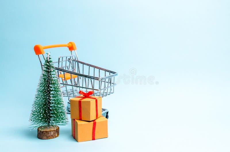 Kerstboom, supermarktkar en gift op een blauwe achtergrond minimalism Familievakantie, Kerstmis en Nieuwjaar Verkoop van giften royalty-vrije stock afbeeldingen