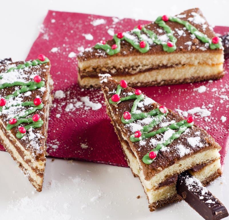 Kerstboom van zoete cake op een witte plaat wordt gemaakt die stock foto