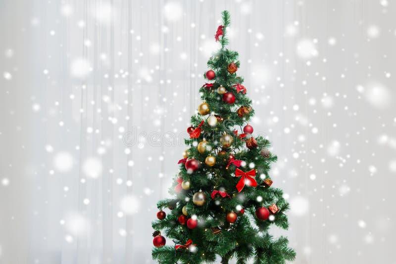 Kerstboom in woonkamer over venstergordijn royalty-vrije stock fotografie