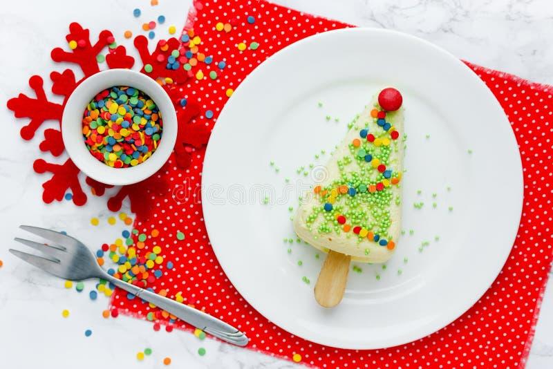 Kerstboomdessert - de gedeeltekaastaart op stok met kleurrijke suiker bestrooit gevormde Kerstmisboom stock afbeelding