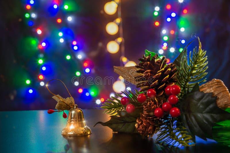 Kerstboomtak en gouden bel met boog en rowanbessen staan op de glanzende tafel/achtergrond Vrolijk kerstfeest royalty-vrije stock afbeeldingen