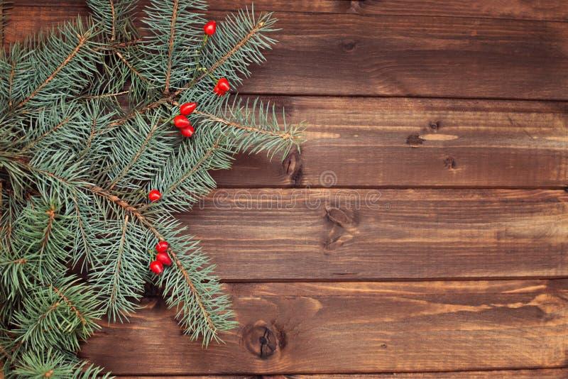 Kerstboomtakken groen met rode bessen op een houten backg stock foto's