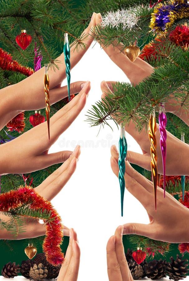 Kerstboomvorm door handen wordt en met verfraaide spartakken en ornamenten dat wordt ontworpen gemaakt die stock afbeelding