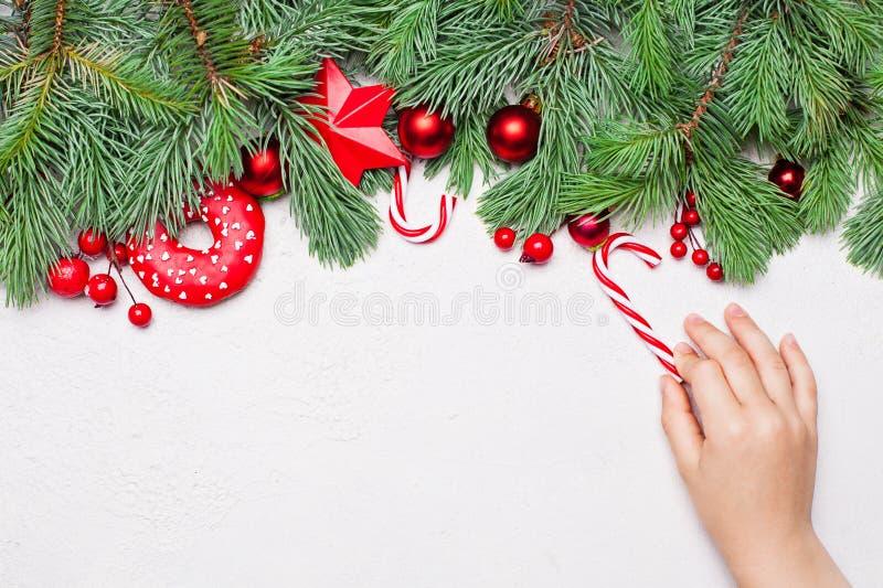 Kerstkaart achtergrondgrenssamenstelling met suikergoedsnoepjes en jong geitjehand Vlak leg, hoogste mening met exemplaarruimte royalty-vrije stock afbeelding