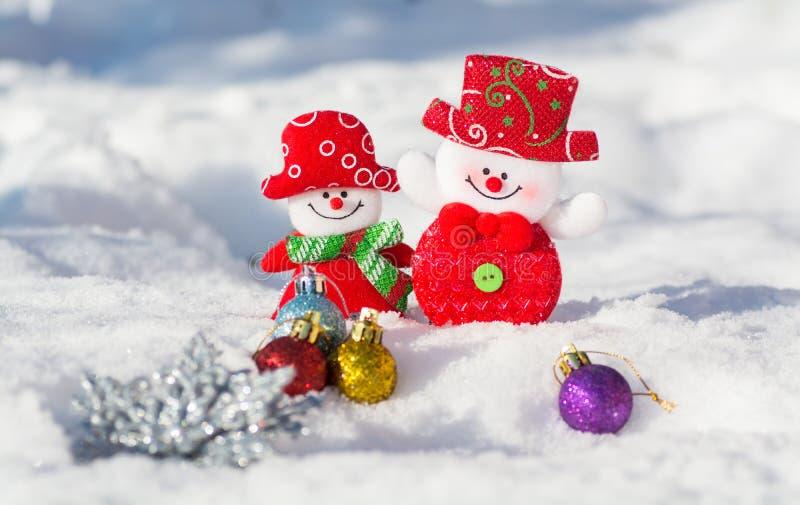 Kerstkaart met sneeuwmannenjongen en meisje met Kerstmis Een paar sneeuwmannen die tegen de achtergrond van sneeuw glimlachen stock fotografie
