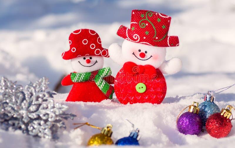 Kerstkaart met sneeuwmannenjongen en meisje met Kerstmisspeelgoed Een paar sneeuwmannen die tegen de achtergrond van sneeuw gliml royalty-vrije stock foto