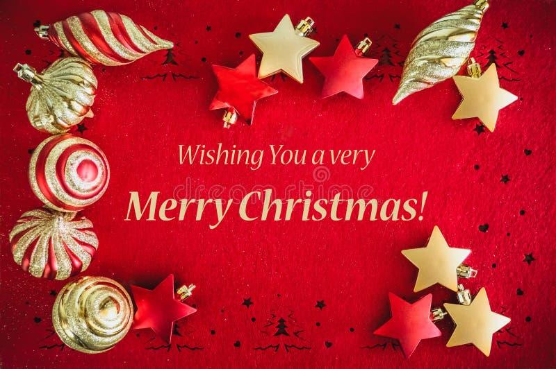 Kerstkaart Rode achtergrond met gouden decoratie, Ballen en Sterren, en het Wensen van Tekst stock afbeeldingen