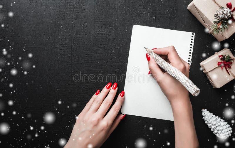 Kerstkaartachtergrond - Vrouwenhanden met rode spijkers die brief met houten potlood schrijven royalty-vrije stock fotografie
