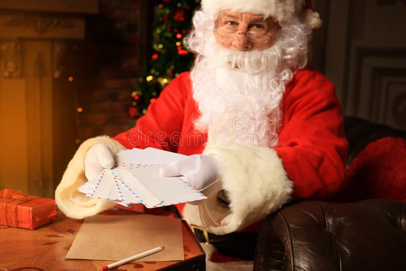 Kerstman die bij de Kerstboom zitten, Kerstmisbrieven houden en een rust hebben door de open haard stock afbeelding