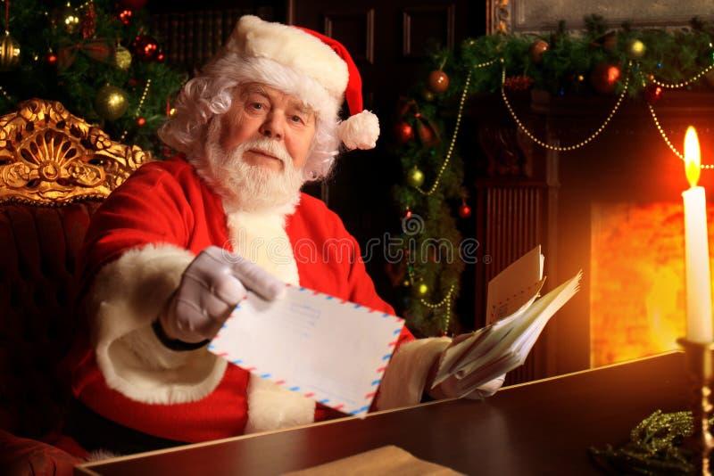 Kerstman die bij de Kerstboom zitten, Kerstmisbrieven houden en een rust hebben door de open haard stock afbeeldingen