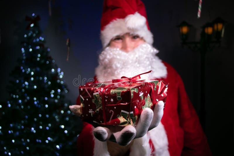 Kerstman die een gift overhandigen aan camera met Kerstmisboom en lichten op achtergrond royalty-vrije stock foto's