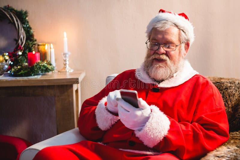 Kerstman die en mobiele telefoon zitten de met behulp van stock afbeeldingen