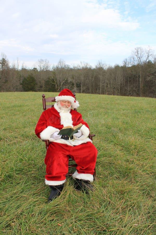 Kerstman die op het Gebied lezen stock foto