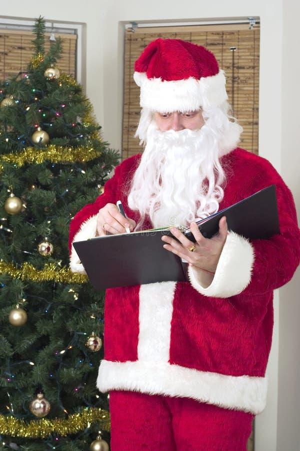 Kerstman die zijn lijst cheking stock afbeelding