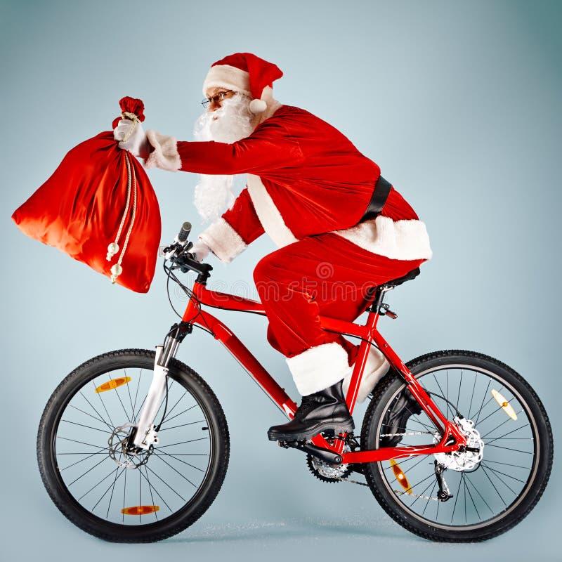 Kerstman met rode zak op fiets royalty-vrije stock foto