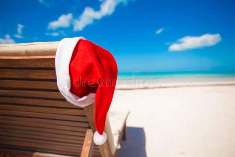 Kerstmanhoed op stoel longue in de tropische Caraïben royalty-vrije stock afbeeldingen