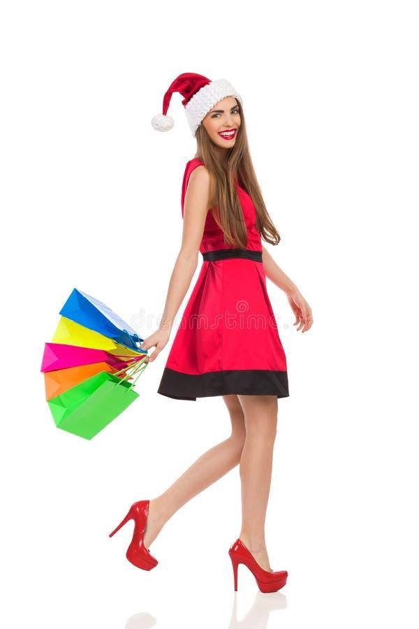 Kerstmanmeisje die met het winkelen zakken lopen stock afbeeldingen