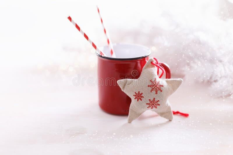Kerstmis als thema gehade ornamenten en rode mok over witte achtergrond stock afbeelding