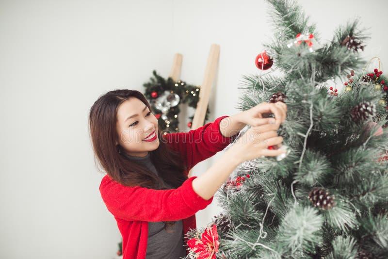Kerstmis Aziatische Mooie Vrouw die nieuw Ce van de Kerstmisboom zich thuis bevinden royalty-vrije stock fotografie