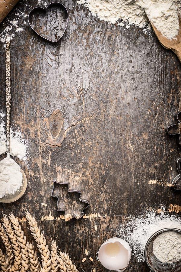 Kerstmis bakt houten achtergrond met koekjesvormen, bloem, keukengereedschap en oren stock fotografie