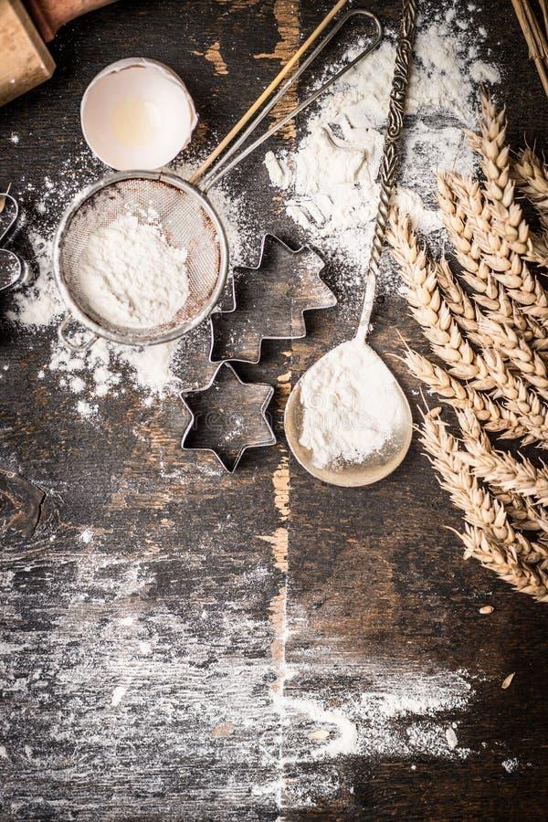 Kerstmis bakt houten achtergrond met ster en de Kerstboom gevormde snijder van het koekjesbaksel, bloem, uitstekende lepel en ore royalty-vrije stock afbeeldingen