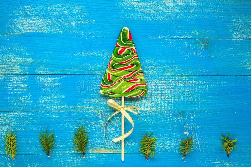 Kerstmis behandelt: kleurrijke lollys in de vorm van sparren op een blauwe houten raad royalty-vrije stock foto