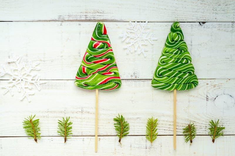 Kerstmis behandelt: kleurrijke lollys in de vorm van sparren op een witte houten raad stock foto's