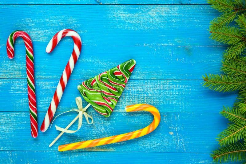 Kerstmis behandelt: kleurrijke lollys in de vorm van sparren, suikergoedriet en groene nette takken op een blauwe houten raad stock foto