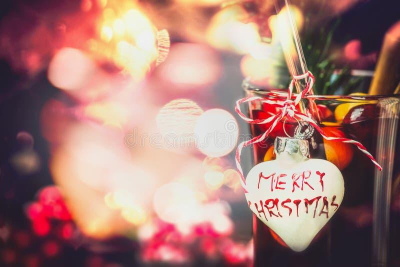 Kerstmis bokeh achtergrond met glas overwogen wijn of stempel met hart en inschrijvings Vrolijke Kerstmis royalty-vrije stock fotografie