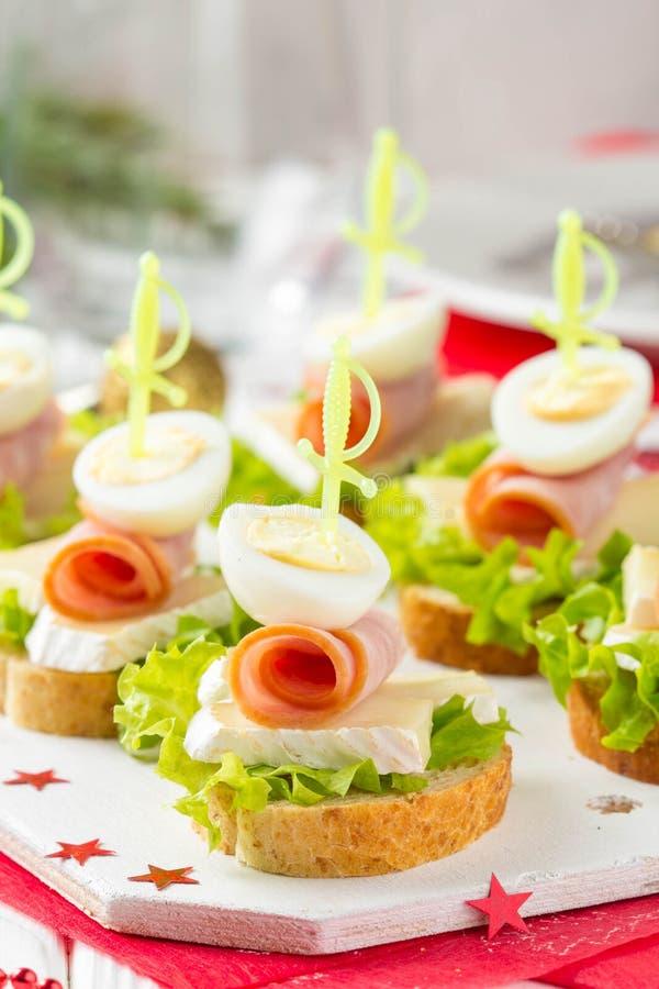 Kerstmis canapes op brood met Brie of Camembertkaas, ham en gekookt kwartelsei Mooie presentatie op het feestelijke nieuwe jaar royalty-vrije stock foto