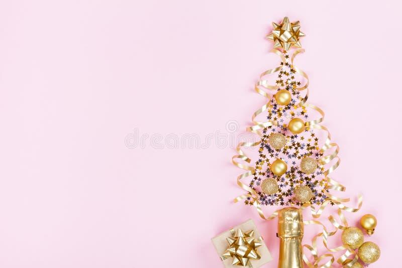 Kerstmis creatieve spar van champagne, confettiensterren en kronkelweg met giftdoos op roze hoogste mening als achtergrond Vlak l stock afbeelding