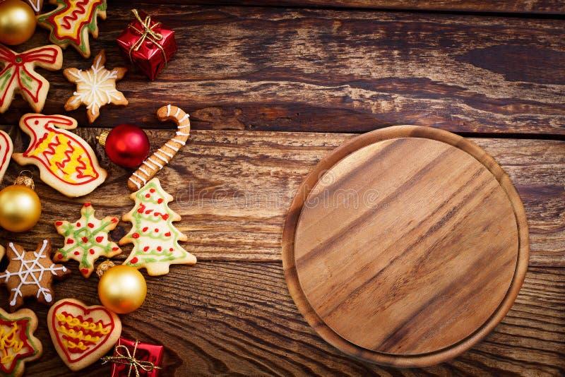 Kerstmis, de achtergrond van het Nieuwjaar Kerstmis houten lijst met koekjes en scherpe raad voor voedsel en pizza Hoogste mening stock afbeeldingen