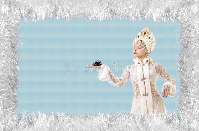 Kerstmis de ontwerp-Kerstmis kaart met een mooie, jonge, glimlachende vrouw kleedde zich als Santa Claus die, door pijnboomnaalde royalty-vrije stock afbeelding