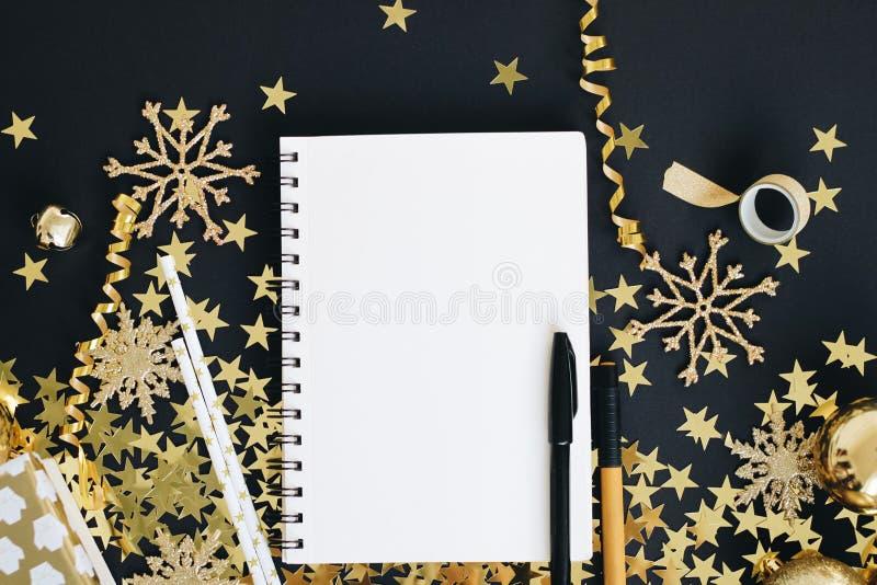 Kerstmis de spot van het planningsconcept omhoog Het notitieboekje op zwarte achtergrond met washiband, goud speelt confettien, g stock fotografie