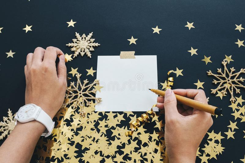 Kerstmis de spot van het planningsconcept omhoog De vrouwenhanden met wath het schrijven nota over zwarte achtergrond met washiba stock foto's