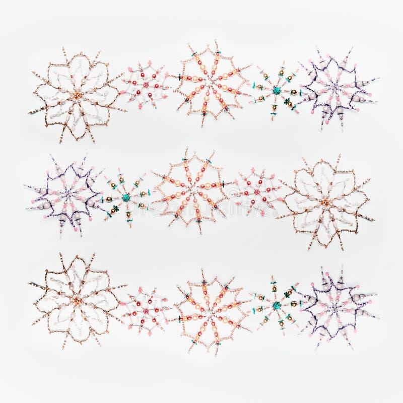 Kerstmis of de winterconcept Het patroon van diverse met de hand gemaakte sneeuwvlokken maakte van parels en bugel op witte burea royalty-vrije stock afbeelding