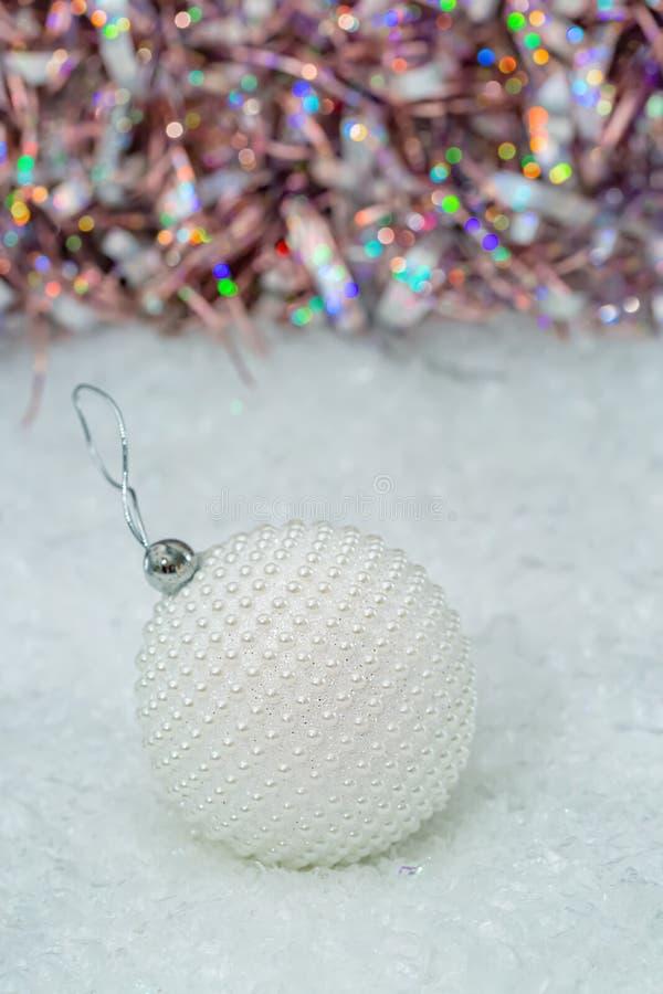 Kerstmis De witte parels van het balpaarlemoer op een sneeuw en een mooie vage kleurrijke achtergrond van het schitteren bokeh me royalty-vrije stock foto