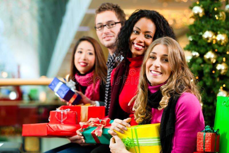 Kerstmis die van vrienden winkelt met stelt in wandelgalerij voor royalty-vrije stock fotografie