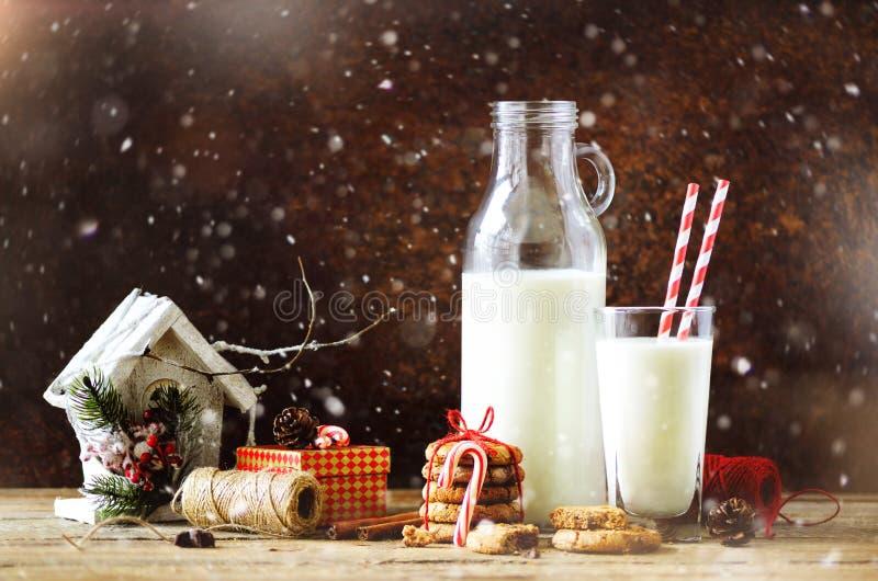 Kerstmis donkere achtergrond met sneeuw en bokeh, exemplaarruimte Fles, glas met melk voor Kerstman, koekjes, rode kabel, anijspl stock foto