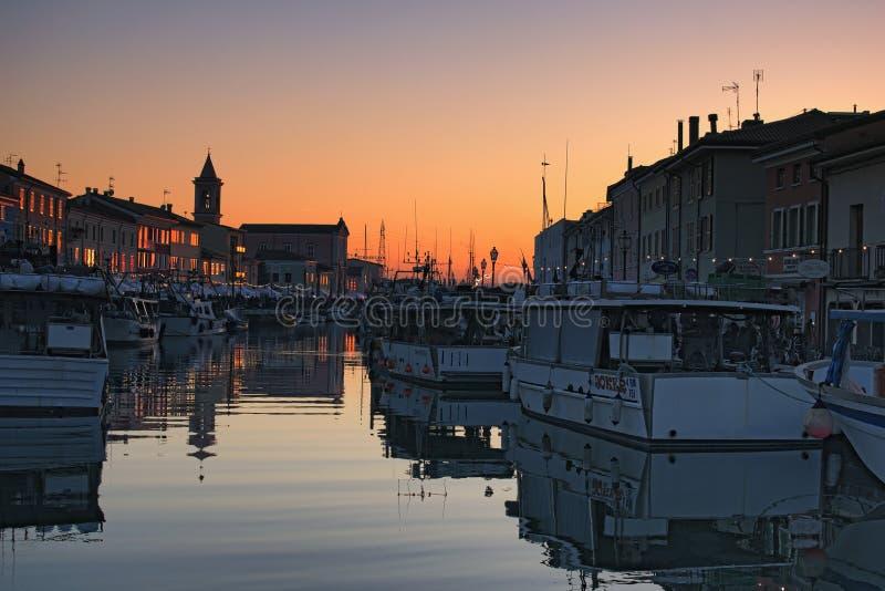 Kerstmis Eerlijke kiosken op de dijk van het havenkanaal met de typische vissersboten van het Adriatische Overzees Magische zonso stock foto's