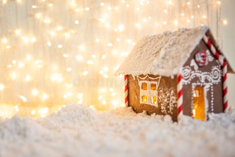 Kerstmis en de nieuwe kaart van de jaargroet Kerstmistak en klokken peperkoekhuis op de achtergrond van slingers royalty-vrije stock foto's